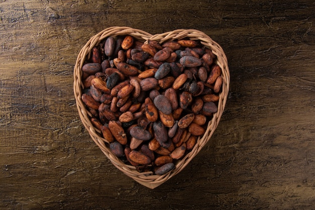 Rohe kakaobohnen im herzförmigen korb mit rustikalem hintergrund