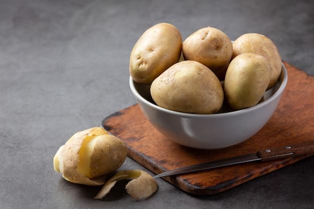 Rohe kartoffel auf dunklem hintergrund