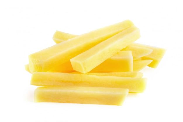 Rohe kartoffel geschnittene streifen bereitete sich für die pommes-frites vor, die über weißem hintergrund lokalisiert wurden.