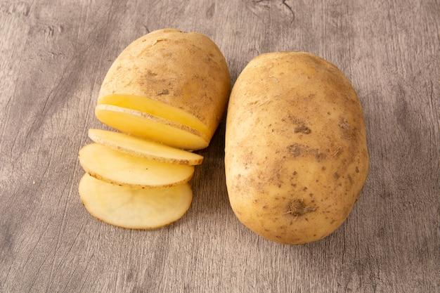 Rohe kartoffel und geschnittene kartoffel über hölzernem hintergrund