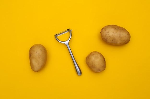 Rohe kartoffel und schälmesser auf gelbem hintergrund. ansicht von oben