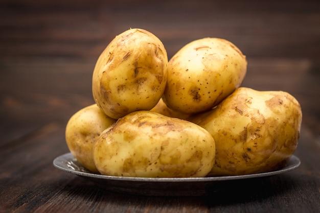 Rohe kartoffeln auf einem braunen hölzernen hintergrund