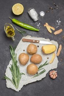 Rohe kartoffeln und eine geschälte kartoffel auf papier mit rosmarin, grünem pfeffer und zitrone auf dem tisch
