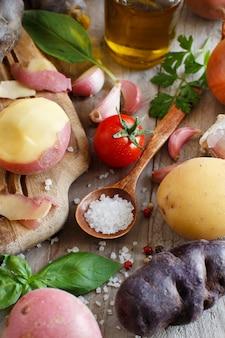 Rohe kartoffeln und gemüse auf einem holzbrett
