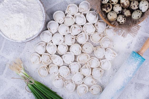 Rohe khinkali-teige auf dem mehl mit einem bund frühlingszwiebeln.