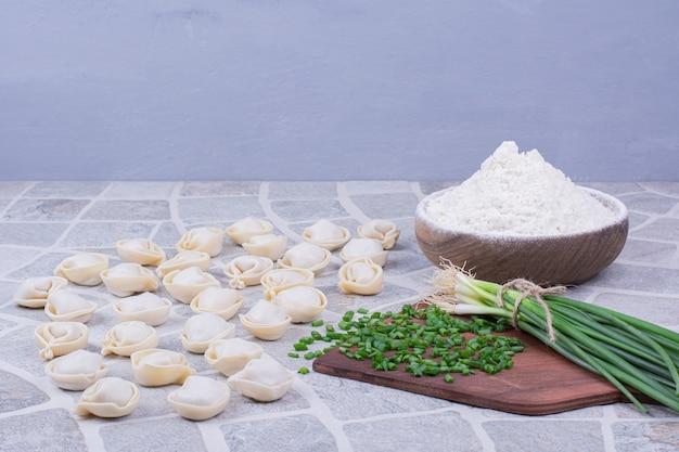 Rohe khinkali-teige auf mehl mit einem bund frühlingszwiebeln.