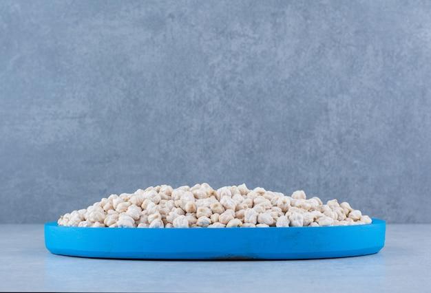 Rohe kichererbsen gehäuft auf einer kleinen blauen platte auf marmoroberfläche