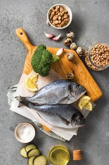 Rohe kochzutaten für leckeres und gesundes essen. frischer fisch, gemüse und hülsenfrüchte auf grauer hintergrundoberansicht
