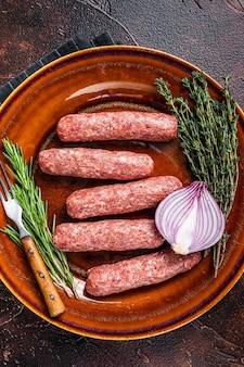 Rohe kofta-fleisch-kebab-würste auf einem teller mit kräutern. dunkler hintergrund. ansicht von oben.