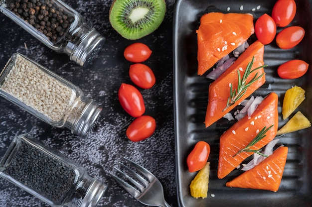 Rohe lachsfilets, pfeffer, kiwi, ananas und rosmarin auf einen teller und schwarzen zementboden.