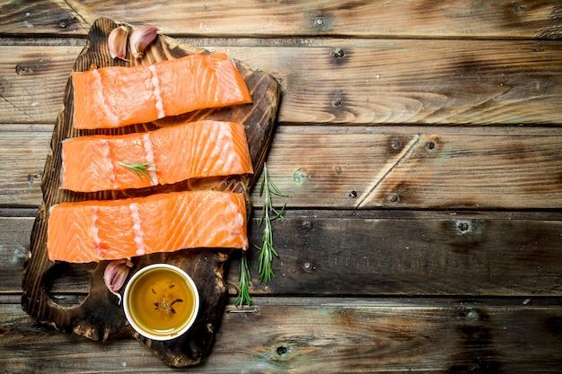 Rohe lachsfischsteaks auf einem schneidebrett mit rosmarin und olivenöl. auf einem holz.