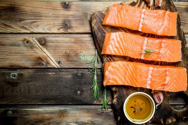 Rohe lachsfischsteaks auf einem schneidebrett mit rosmarin und olivenöl.