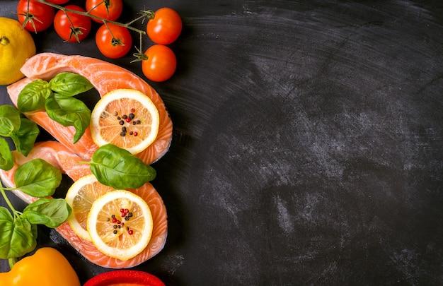 Rohe lachssteaks und frische zutaten zum kochen auf dunklem hintergrund.