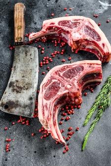 Rohe lammkoteletts frisch geschnitten mit fleischbeil. schwarze oberfläche. draufsicht