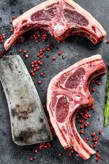 Rohe lammkoteletts frisch geschnitten mit fleischbeil. schwarzer hintergrund. draufsicht