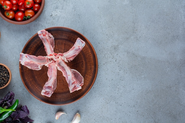Rohe lammrippen mit gemüse und gewürzen auf einem steintisch.