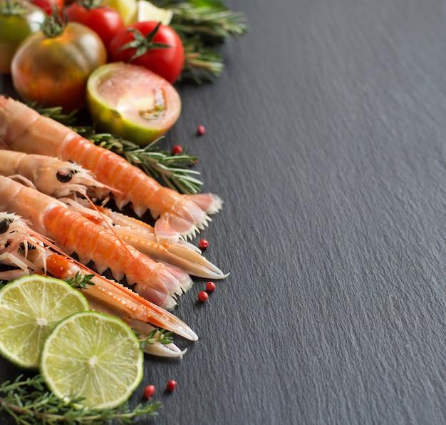 Rohe langustinen mit gemüse und kräutern auf dunklem tisch