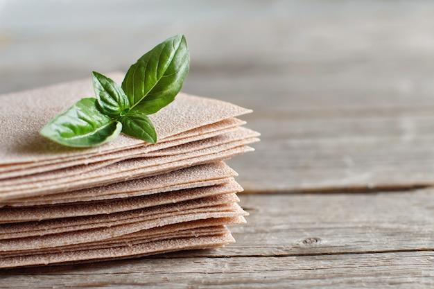 Rohe lasagneblätter und basilikumblätter auf einem holztisch schließen oben