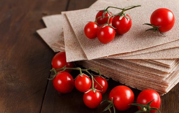 Rohe lasagneblätter und kirschtomaten auf einem holztisch