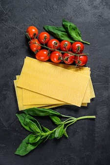 Rohe lasagneblätter. zutaten basilikum, kirschtomaten. schwarzer hintergrund. ansicht von oben. platz für text