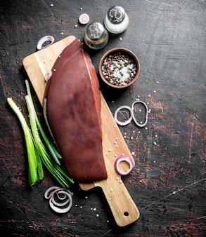 Rohe leber auf einem schneidebrett mit frühlingszwiebeln, gewürzen und zwiebelringen. auf dunklem rustikalem tisch