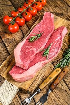 Rohe lendenstückkappe oder picanha-steak auf einem schneidebrett.