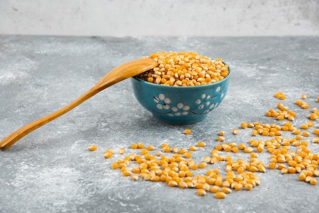 Rohe maiskörner in blauer schüssel mit holzlöffel.