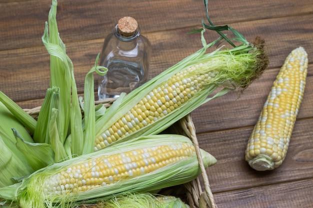 Rohe maiskolben mit maisseide und blättern im weidenkorb. wasserflasche. hölzerner hintergrund. flach legen