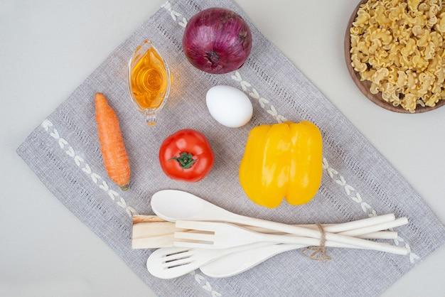 Rohe makkaroni mit gemüse auf holzteller auf tischdecke