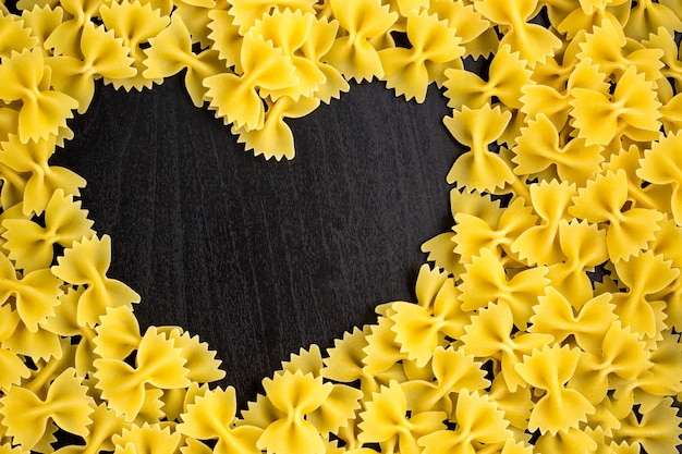 Rohe makkaroni - pasta farfalle. in der mitte des leeren raumes in form eines herzens