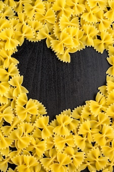 Rohe makkaroni - pasta farfalle. mitten im leeren raum in form eines herzens