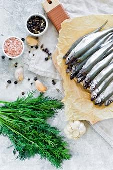 Rohe makrele auf einem hölzernen hackenden brett, einem dill, einem rosa salz, einem pfeffer und einem knoblauch.
