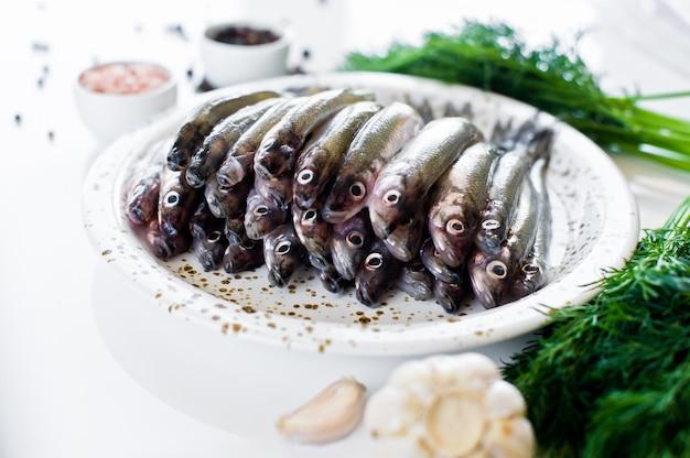Rohe makrele auf einer platte, einem dill, einem rosa salz, einem pfeffer und einem knoblauch.