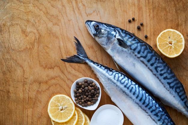 Rohe makrele mit zitrone und gewürzen auf einem hölzernen hintergrund