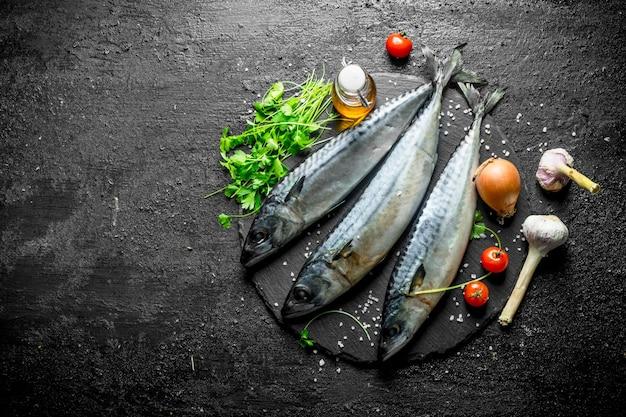 Rohe makrele mit zwiebeln, petersilie, knoblauch und tomaten. auf schwarzem rustikalem tisch