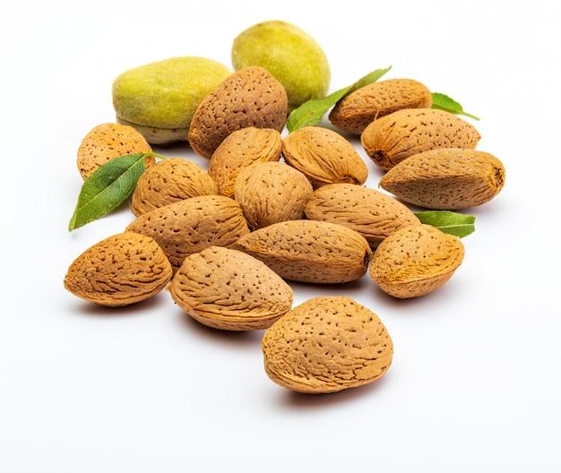 Rohe mandeln, geschält, mit schale, haut (almendrucos) und mandelblättern. isoliert