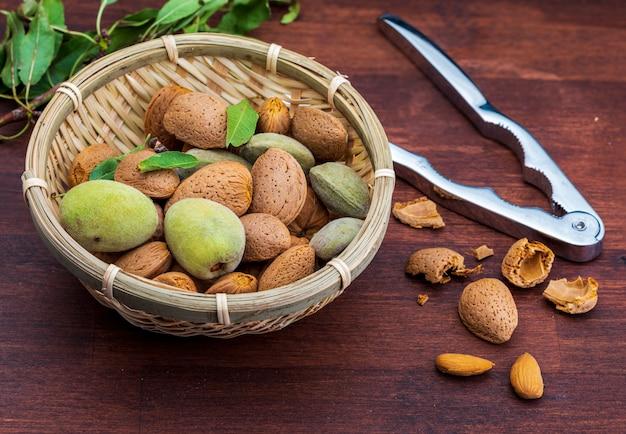 Rohe mandeln, geschält, mit schale, haut (almendrucos) und mandelblättern.