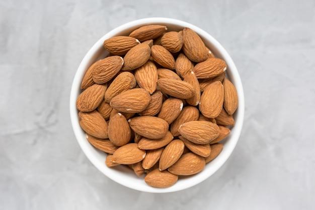 Rohe mandeln in einer porzellanschale auf einer grauen oberfläche, konzept der gesunden ernährung veganes essen. nahaufnahme, selektiver fokus, kopierraum.