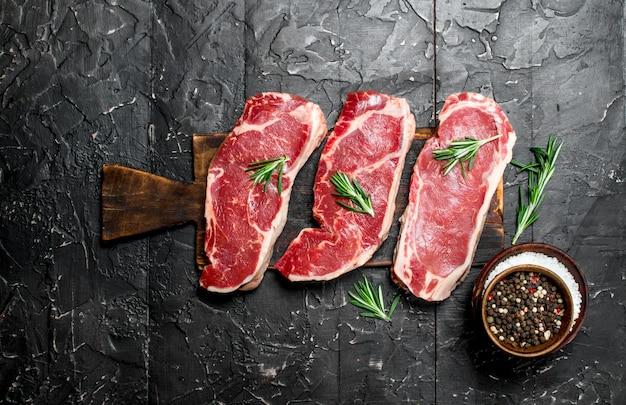 Rohe marmorierte rindfleischsteaks mit salz und gewürzen auf einem dunklen rustikalen tisch.
