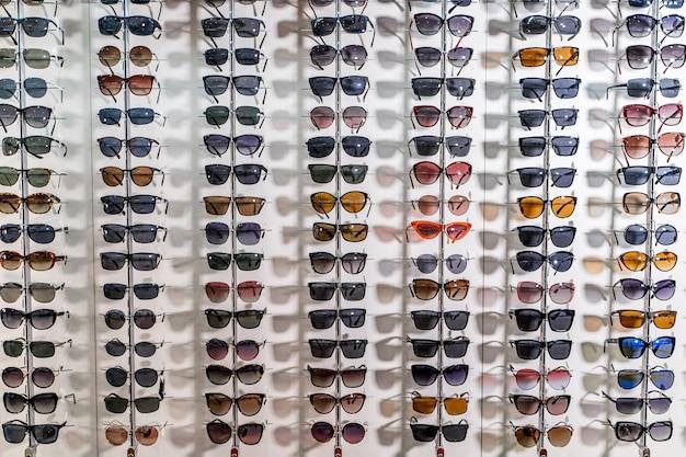 Rohe mode-eleganz-sonnenbrille im laden. vitrine mit sonnenbrille im modernen augengeschäft. nahansicht.