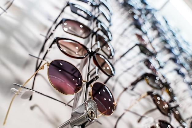 Rohe mode-eleganz-sonnenbrille im laden. vitrine mit sonnenbrille im modernen augengeschäft. nahaufnahme.