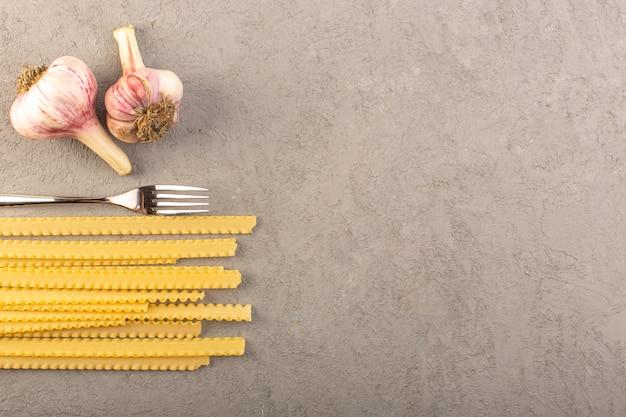 Rohe nudeln der draufsicht gelbe trockene lange italienische nudeln zusammen mit knoblauch und gabel lokalisiert auf dem gemüsemahlzeitgemüse des grauen hintergrunds