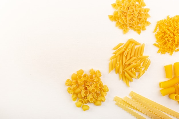 Rohe nudeln der draufsicht trocknen italienische gelbe nudelsammlung und verteilen sich auf dem weißen hintergrund italienisches essen mahlzeit