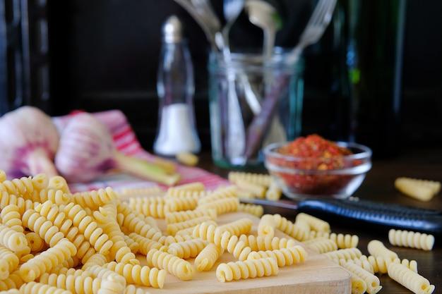 Rohe nudeln, gewürze, knoblauch. das konzept der italienischen küche. vegetarisch kochen.