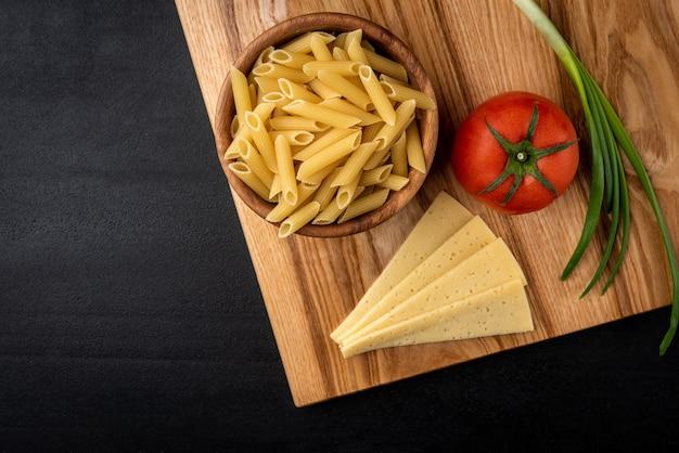 Rohe nudeln in holzschale mit käse, tomaten und frühlingszwiebeln auf schwarzem hintergrund.