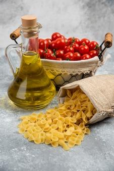 Rohe nudeln mit einem korb kirschtomaten und einer flasche olivenöl.