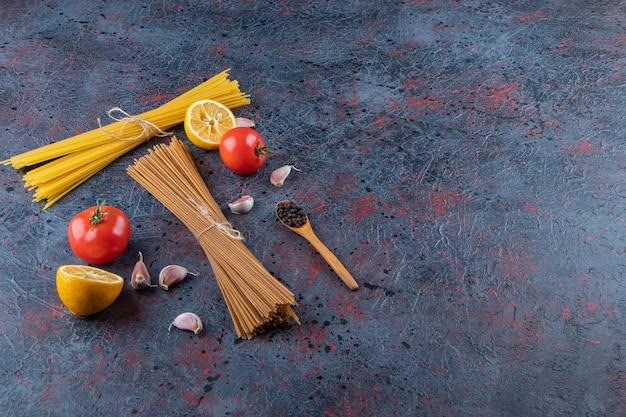 Rohe nudeln mit frischen roten tomaten und knoblauch auf dunklem hintergrund.