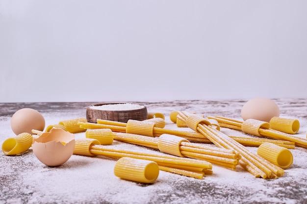 Rohe nudeln mit mehl und eiern auf dem holztisch.