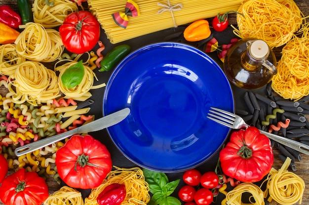 Rohe nudeln mit zutaten und kopierfläche auf leerem blauen teller mit stahlgabel und messer