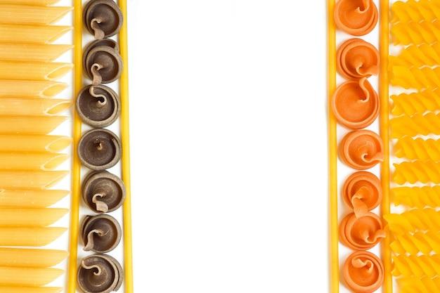 Rohe nudeln und spaghetti in verschiedenen farben und sorten sind in einer vertikalen linie angeordnet.